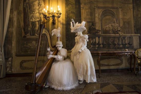 Venedik Karnavalı sırasında, geleneksel kostümleri giyen iki kişi sarayın içinde arp ile poz veriyor