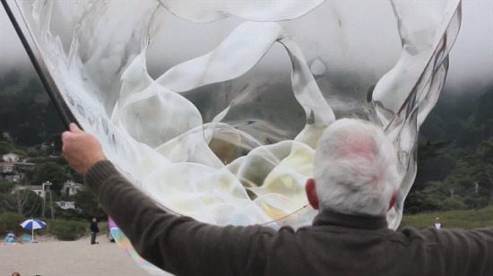 Dev baloncuklarla çocukları eğlendiren yaşlı amca