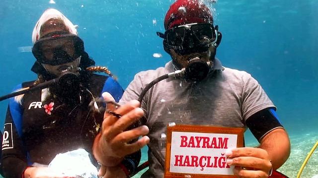 Su altında bayramlaşma merasimi: Harçlık vermeyi ihmal etmediler