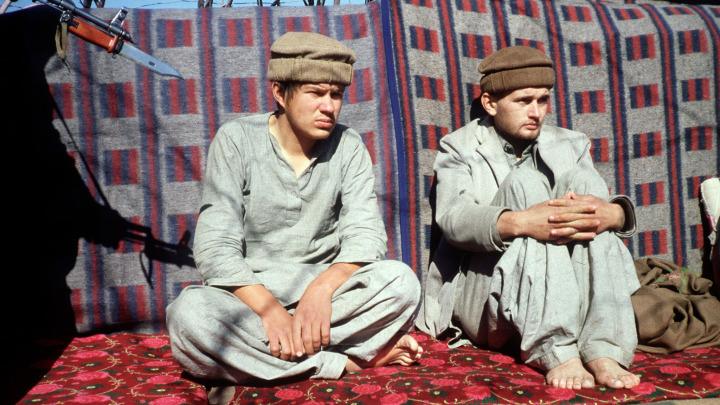 Afganlara esir düşen yerel kıyafetler giydirilmiş iki Sovyet pilotu.