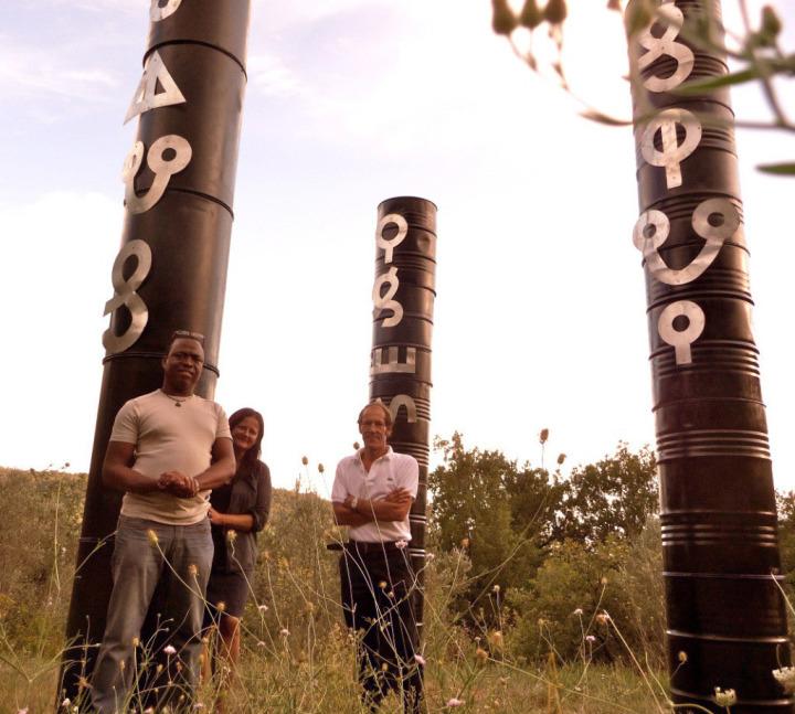 """Surinamlı sanatçı Marcel Pinas'ın unutulmakta olan Afaka dilinde """"İçme Suyumuzu Koru """" yazan petrol kuyusu heykelleri."""