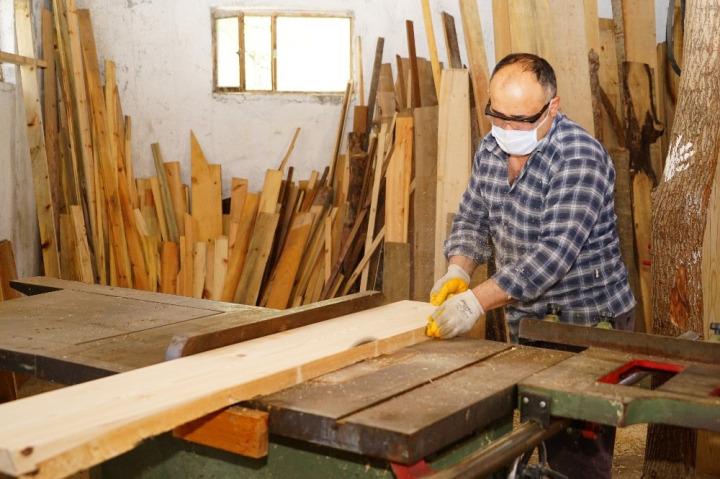 Bir marangoz ustası çalıştığı sırada görülüyor.