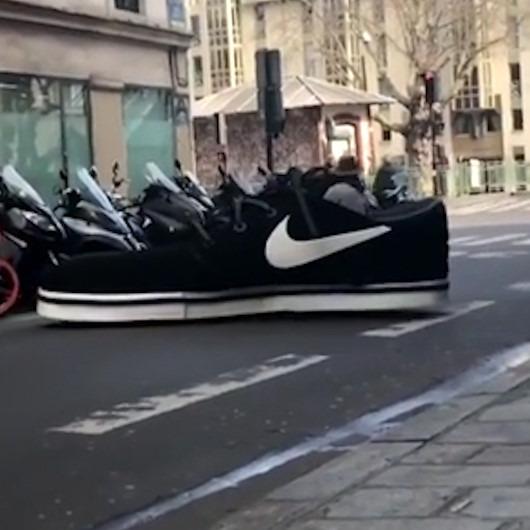 Dev ayakkabının içinde Paris sokaklarını turlayan adam
